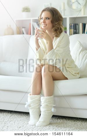 Full lenght portrait of young beautiful woman with a cup of tea sitting on sofa at home