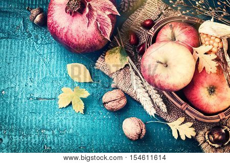 Autumn frame with pomegranate apple and fall leaves over blue wooden background. Fall background with copy space