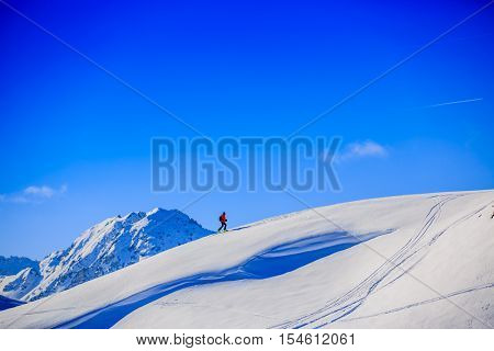 Ski touring in high mountains in fresh powder snow in sunny day. Snow mountain range. Mt Fort Peak Alps region Switzerland.Wallis