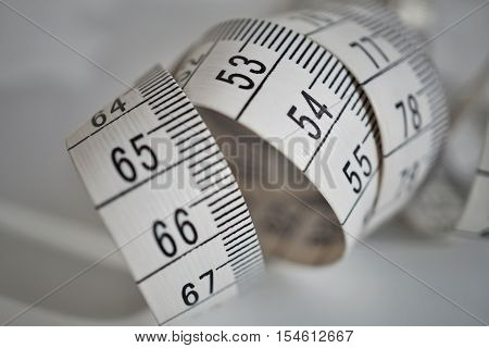 Isolated white tape measure (tape measuring length in meters and centimeters) as symbol of tool used by tailor and people reducing weight during diet
