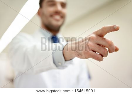 profession, people, medicare, healthcare and medicine concept - close up of happy medic or doctor pointing finger at hospital corridor