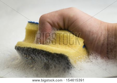 Close up of a Hand with a yellow Sponge. Sponges. Kitchen work,