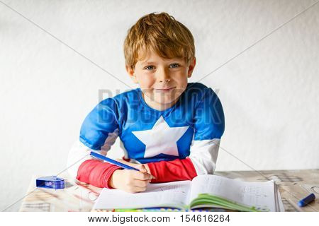happy school kid boy with super herocostume at home making homework. Little child writing with colorful pencils, indoors. Elementary schoo, education concept.