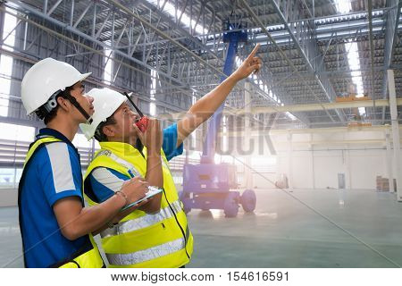 Quality control of pro industrial engineer 2 person working in the factory with talking on the walkie-talkie and write on paper memo for controlling work