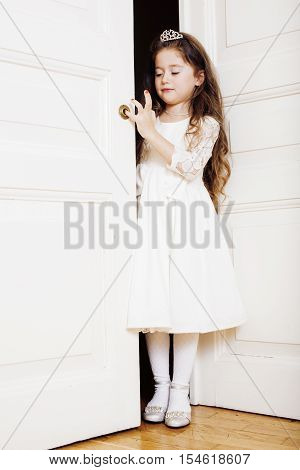 little cute girl at home, opening door well-dressed in white dress and tiara, adorable milk fairy teeth