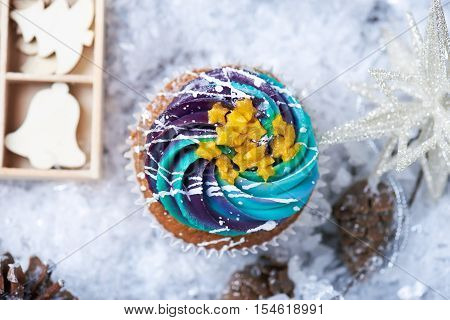 Winter cupcakes with gradient cream and golden stars on a snow with presents, wooden toys, cone and snowflakes on a background. Winter mood. Top view poster