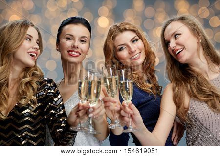 celebration, friends, bachelorette party and holidays concept - happy women clinking champagne glasses over lights background