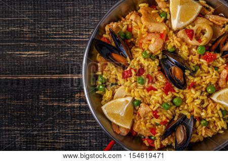 Paella with chicken seafood vegetables and saffron served in the traditional pan top view.