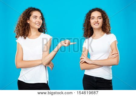 Girl pointing finger at her sister twin over blue background. Copy space.