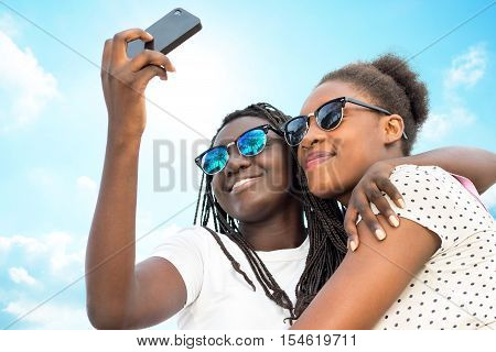 Close up portrait of two diverse african teen girls wearing sun glasses taking self portrait with phone against blue sky.