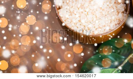 beauty, spa, bodycare, bath and natural cosmetics concept - close up of himalayan pink salt in wooden bowl with leaves over lights and snow