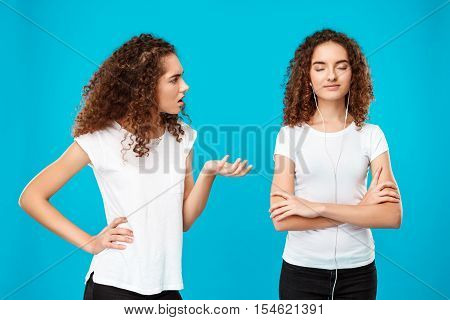 Girl raging, resenting at her sister twin in headphones over blue background. Copy space.