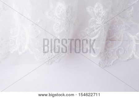 Close-up of lace wedding veil on white wooden backgroundhair accessories. Top view with copy space.