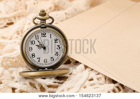 Vintage pocket watch with blank paper on lace background