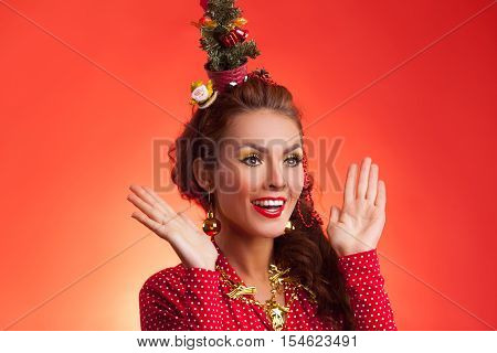 New Year's and Christmas efforts and preparations.Surprised Happy Girl with New Year tree instead of santa hat on head thinks about winter holidays celebration. Woman arranging decorations of Xmas tree. Creative fun studio photo.