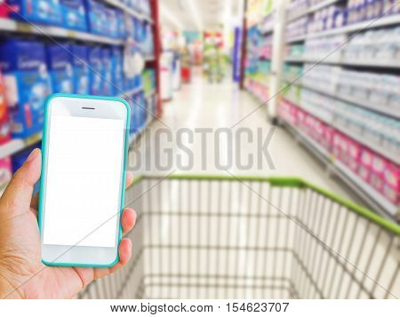 left hand holding green mobile phone with supermarket blur background online shopping concept.