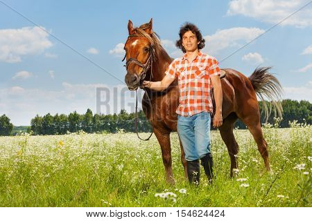 Full length portrait of young man holding his brown horse by a bridle at flowery meadows