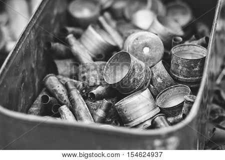 pile of old rusty shell casings from assault rifles and mounted grenade launchers in metal box black and white photo
