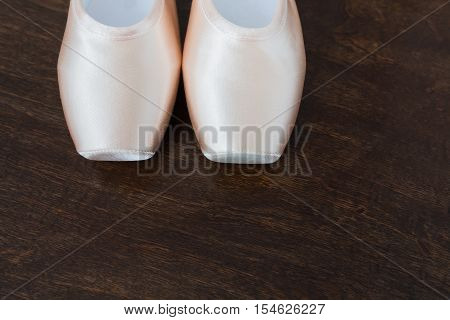 Pastel pink ballet shoes background. New pointe satin pastel pink shoes platform closeup lay on dark brown rustic wood. Ballet details