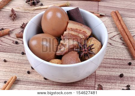 Thai Recipes : Stewed boiled egg with tofu and streaky pork ,call Khai Palo in Thai, take photo with herbs as Chinese star anise ,cinnamon,black pepper,cilantro roots and stems . Selective focus.