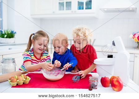 Cute kids adorable little girl boy and funny baby making dough for a cake. Children mix flour eggs and milk baking apple pie in sunny white kitchen with modern appliances. Family cooking at home.
