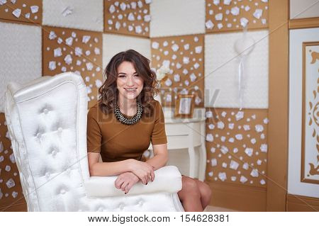 portrait of fashionable model young woman sitting in a white chair. Business, elegant businesswoman. Interior, furniture.