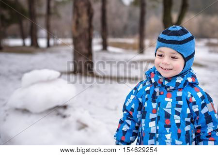 Winter portrait of kid boy in colorful clothes outdoors during snowfall. Active outoors leisure with children in winter on cold snowy days. Happy toddler child having fun with snow in forest