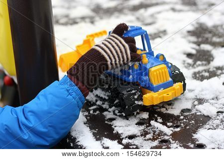 Part of the image of a small child that walks on the Playground and plays with the bright plastic toy car-bulldozer. Visible hand dressed in a blue jacket and glove.