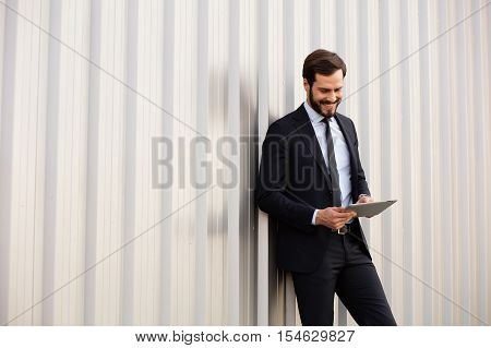 Smiling Man With Tablet Outside