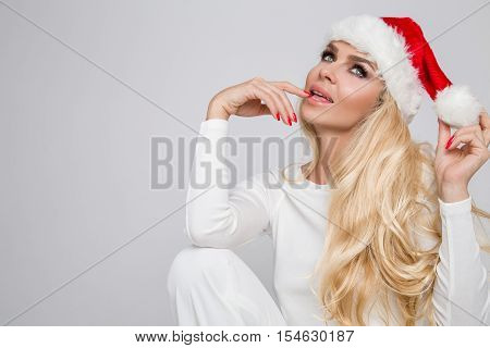 Beautiful Sexy Blonde Female Model Dressed As Santa Claus In A Red Cap With A Tassel At The White Fu