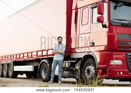 handsome masculine driver with beard wearing jeans standing with folded arms next to his truck and looking with confidence at camera poster