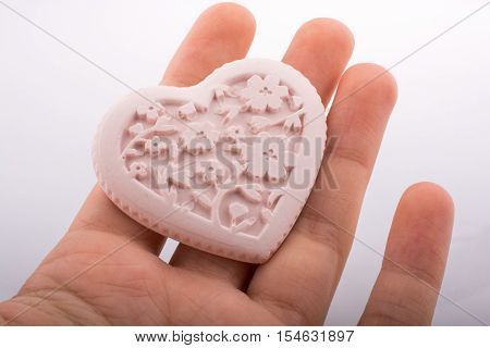 Heart shaped stone object held in hand on white background