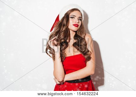 Portrait of a beautiful sexy brunette woman in red christmas dress standing isolated over white background
