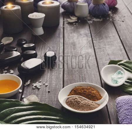 Spa treatment tools and aromatherapy concept background. Zen stones, aroma salt, spices, herbs, oil and soap, burning candle and details of wellness body care and alternative indian medicine.