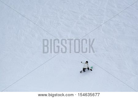Snowboarder makes tricks while he rides from the mountain. A lot of free space on image for an additional info.