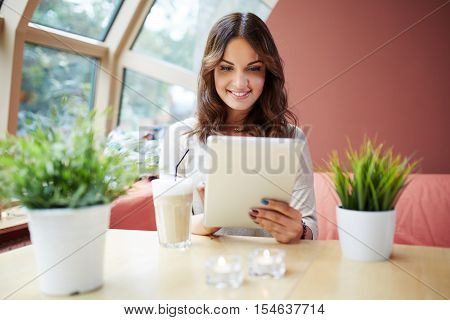 Pretty Girl Using Tablet At Cafe