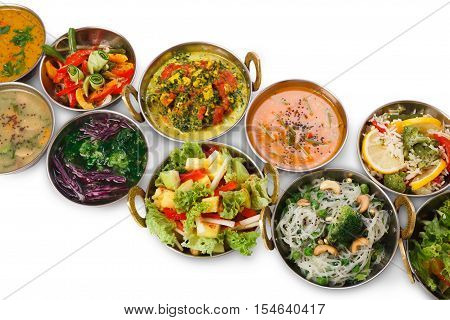 Vegan and vegetarian restaurant dishes, hot spicy and creamy indian soups, salads, rice vermicelli in copper bowls. Traditional indian cuisine meals isolated on white background. Healthy eastern food