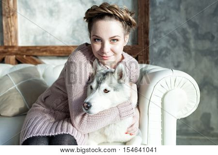 Young beautiful pregnant woman huging husky dog on the sofa