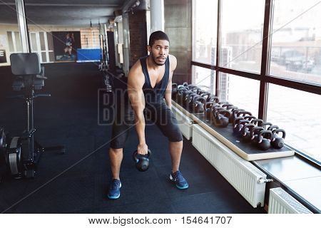 Healthy fitness man doing a weight training by lifting a heavy kettlebell in the gym