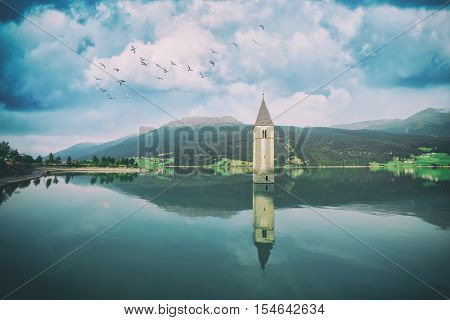Beautiful view of the lake Resia. Famous tower in the water. Alps, Italy, Europe. Toned like Instagram filter