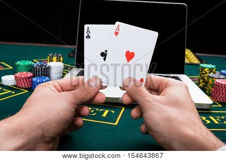 casino, online gambling, technology and people concept - close up of poker player with playing cards, notebook and chips at green casino table. first-person view. two aces, a winning combination