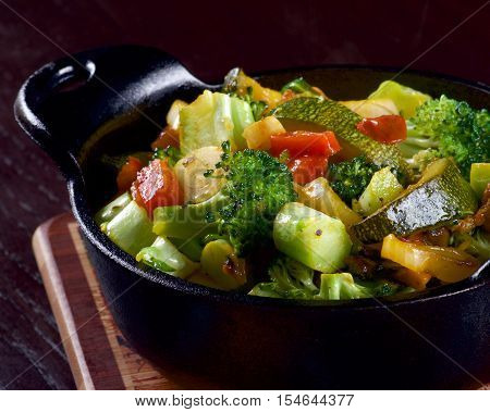 Homemade Colorful Vegetables Ragout with Zucchini Carrots Broccoli Leek and Red Bell Pepper in Black Iron Stewpot on Wooden Cutting Board Cross Section on Dark Wooden background