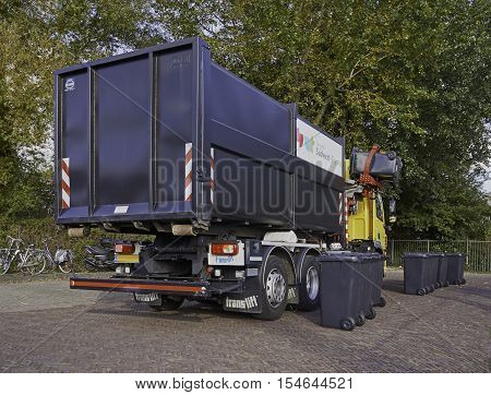 SNEEK, THE NETHERLANDS - OCTOBER 29, 2016: A recycling truck picking up two grey bins from a row of bins on the street. With a side loader the driver operates the mechanical gripper from his cabin.