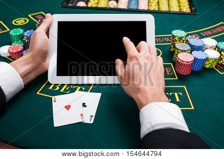 casino, online gambling, technology and people concept - close up of poker player with playing cards, tablet and chips at green casino table. first-person view. two aces, a winning combination