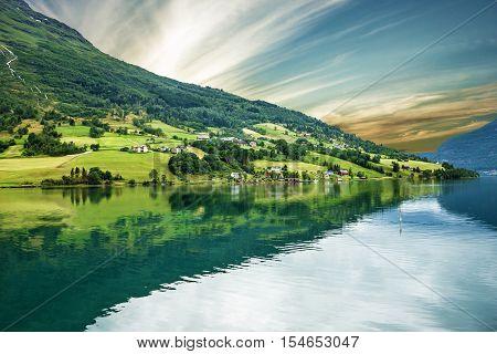 Norway, Olden village, green hills seaside. Norwegian fjord in summer.
