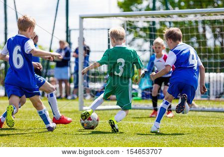 Football soccer match for children. Boys playing football game on a school tournament. Dynamic action picture of kids competition during playing football. Sport background image.