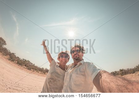 Adult couple taking selfie in the Namib desert Namib Naukluft National Park main travel destination in Namibia Africa. Fisheye view in backlight adventures in Africa. Toned image.