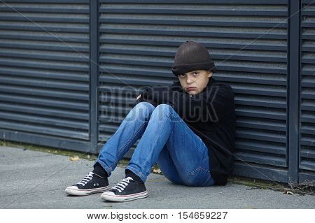 dramatic portrait of a little homeless boy on the street poverty city poster