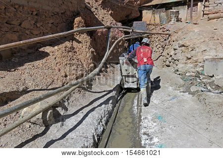 Silver miners pushing the cart into the mines of cerro Rico, Potosi Bolivia