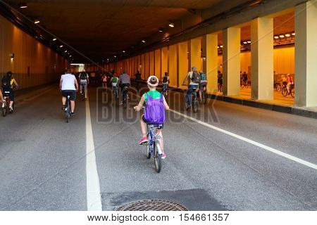 Many people ride bicycle in tunnel during bike parade in city, back view
